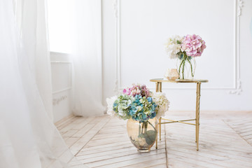 Tender simple  interior in light colors with tule, bouquets of artificial hydrangea and elegant  mirror table on light parquet floor
