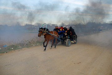 Migrants travel on a horse carriage near the Turkey's Pazarkule border crossing in Edirne