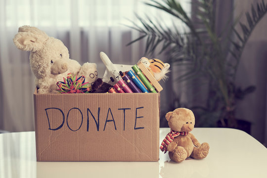 Donation box with children toys. woman collects toys for charity.