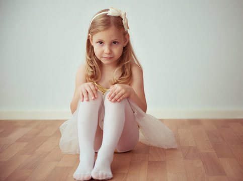 Cute little blonde girl sitting in ballet tutu