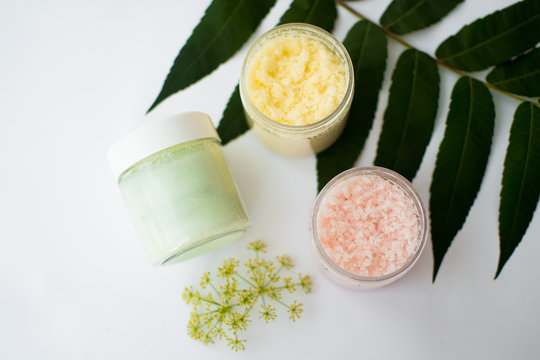 Cosmetic jars of green, yellow, pink scrub with leaf and flower on white background. Natural organic cosmetics