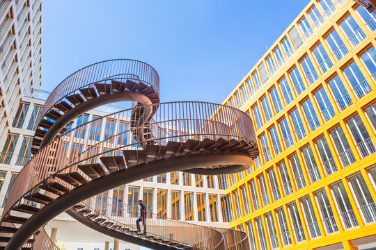 Germany, Bavaria, Munich, The Endless or Infinite Staircase sculpture by Olafur Eliasson with KPMG offices behind