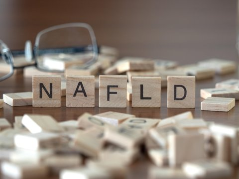 the acronym nafld for Non-alcoholic fatty liver disease concept represented by wooden letter tiles on a wooden table with glasses and a book