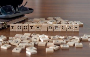 tooth decay concept represented by wooden letter tiles on a wooden table with glasses and a book