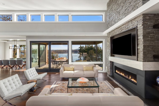 Beautiful living room in new luxury home with large stone fireplace surround, tv, and abundant natural light. Features exterior view of water.