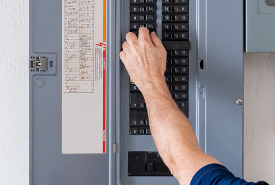 Resetting tripped breaker in residential electricity power panel. Electrician turning off power for electrical outlet at circuit breaker box.