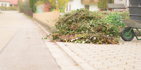 Garden waste from cutting shrubs and plants. Standing by the road and waiting to be picked up. Garden waste collection