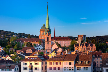 Fototapete - Aerial view over roofs and towers of Old Town of Zurich, the largest city in Switzerland at sunset.