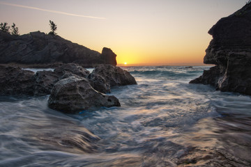 Sun breaking the horizon over a rocky cove on an isolated beach in Bermuda - Jobsons Cove. Sunrise with water swirling In foreground Fotobehang
