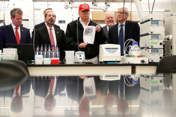 U.S. President Trump displays a photo of the COVID-19 Coronavirus beside Georgia Governor Kemp. HHS Secretary Azar and C.D.C. Associate Director for Laboratory Science and Safety Monroe at the during a tour of the CDC in Atlanta