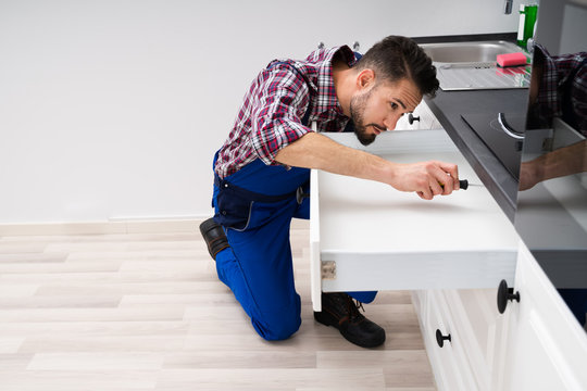 Carpenter Fixing Drawer In Kitchen