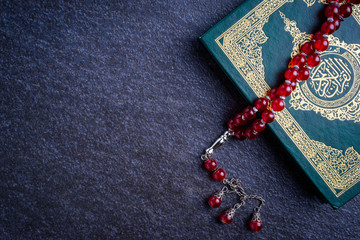"Eid Mubarak or Islamic concept. The Islamic holy book, Quran or Kuran, with rosary beads or ""tasbih"" on grey background. Arabic words on the book means ""Holy Quran""."