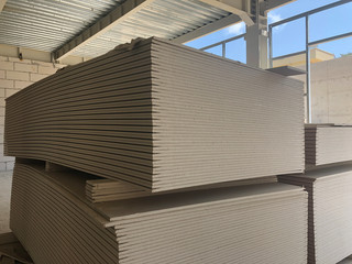 Piled sheets of drywall at the construction site. Stacked plasterboard sheets. Gypsum cardboard
