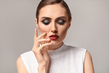 Wall Mural - Young woman with beautiful makeup on grey background