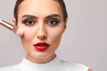 Wall Mural - Beautiful young woman applying makeup against grey background