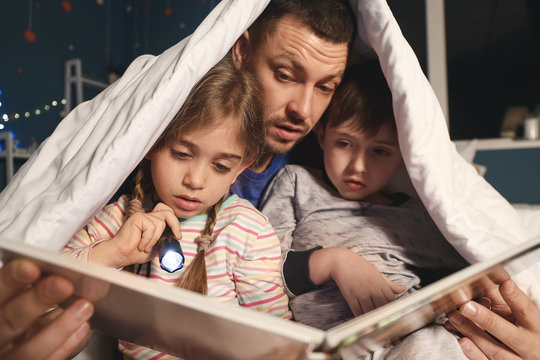 Father and his little children reading bedtime story at home