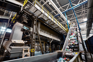 GRODNO, BELARUS - OCTOBER 2018: recycling plant conveyor belt transports garbage inside drum filter or rotating cylindrical sieve with trommel or sorting pieces of garbage into various sizes fractions
