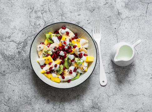 Coconut yogurt and tropical fruit salad for breakfast, snack, dessert. Salad with greek yogurt, banana, mango, kiwi, pomegranate seeds and flaxseeds on a gray background. the view from the top