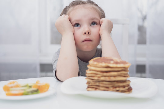 Diet for children. Sad and unhappy little girl. A child looks at a stack of pancakes.