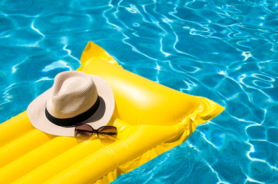 Sun hat and sunglasses resting on bright yellow inflatable raft floating in blue swimming pool
