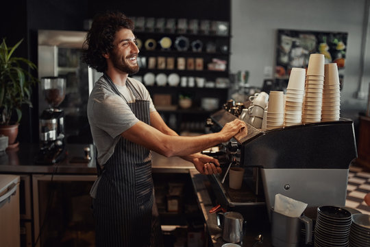 Young cheerful barista wearing black apron while preparing coffee at an automatic machine in a modern coffee shop