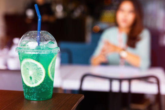 Iced green Italian soda with sliced lemon on the wooden table. Selective cold drink menu with blur woman.
