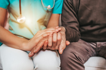 Female carer consoling a senior patient at the nursing home. Closeup shot of a young woman holding a senior man's hands in comfort. Female healthcare worker holding hands of senior man at care home