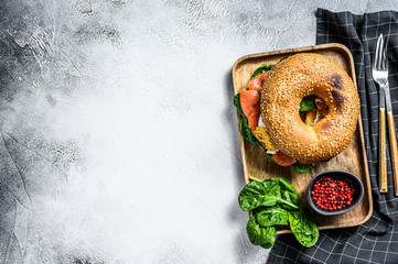 Bagel sandwich with salmon, cream cheese, spinach and egg on a wooden plate. Gray background. Top view. Copy space