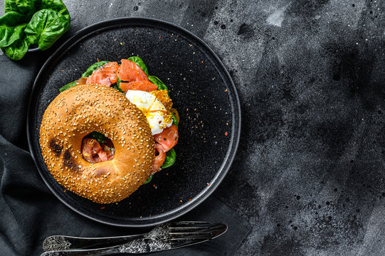 Smoked salmon bagel toasts with soft cheese, spinach and egg. Black background. Top view. Copy space