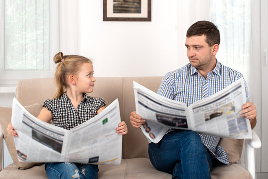 Young girl with  her dad sitting on the sofa at home and reading the newspaper together same way.  Daughter imitates her father.
