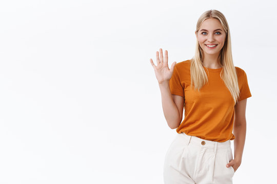 Friendly, carefree sassy attractive blond woman in orange t-shirt, pants raise palm and waving hand in greeting gesture, smiling joyfully say hi or hello, welcome you or guest, white background