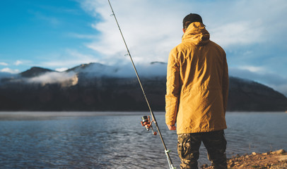 fishery concept, fisherman enjoy hobby sport, fishing rod on evening lake, person catch fish on background blue sky, holiday relaxation vacation