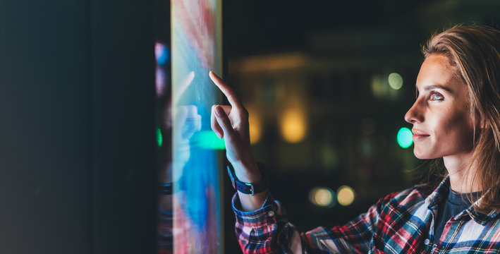 girl pointing finger to blank monitor display, hipster touch multimedia technology on light night city, click media lcd device, mockup screen information gadget