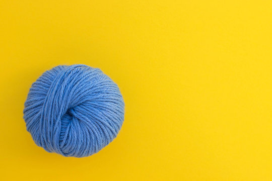 Ball of blue wool yarn on bright yellow background. Knitting, handmade and hobby concept. Flat lay, top view with copy space.