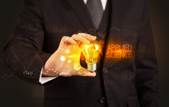Businessman holding lightbulb with APPLIED SCIENCE inscription, Business technology concept