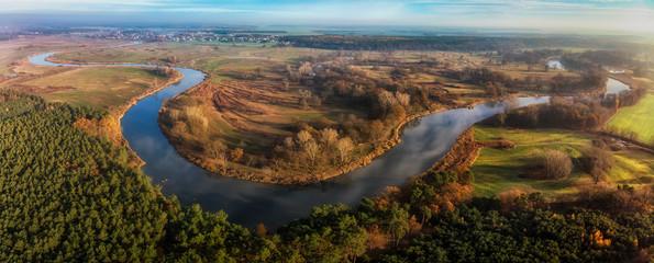Wijąca się rzeka Warta wśród łąk i lasów Wielkopolski, widok z lotu ptaka
