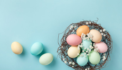 Pastel Easter eggs in nest on blue background top view. Flat lay style.