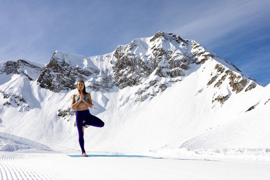 A young woman practice yoga in mountains. With a great view of snow and winter landscape.