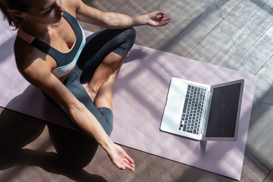 Top view young sporty slim woman coach video online training hatha yoga instructor modern laptop mockup screen meditate Sukhasana posture relax breathe easy seat pose gym healthy lifestyle concept.