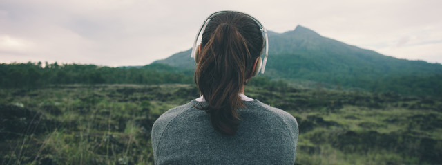 Woman in headphones listening music in nature and at the mountain Fotomurales