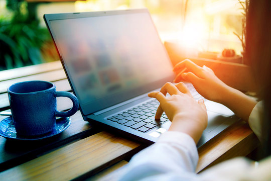 woman hand working on computer laptop with coffee cup beside