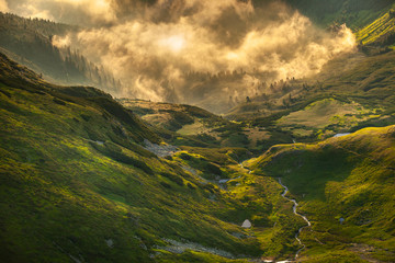 Epic mountain landscape, mist over grass land and river at sunrise