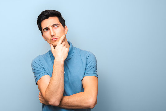 what can I do. pensive man in blue polo shirt against a blue background with hand on his chin and looking up with copy space