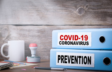 COVID-19, CORONAVIRUS and PREVENTION. Two binders on desk