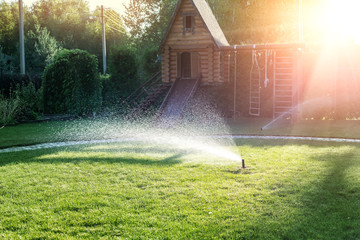 Fotorollo Lachs Landscape automatic garden watering system with different sprinklers installed under turf. Landscape design with lawn hills and fruit garden irrigated with smart autonomous sprayers at sunset time