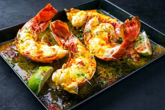 Traditional barbecue spiny lobster tail sliced and offered with saffron lemon sauce as closeup in a metal try