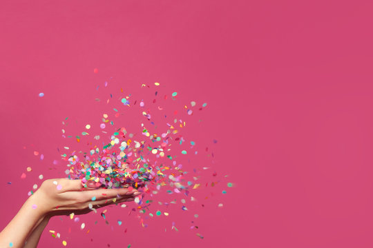 Falling confetti on bright pink background