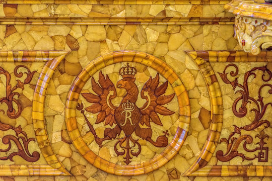 Detail view of the eagle coat of arms of the Prussian kings on amber wall panels in the restored Amber Room (Amber Chamber) in the Catherine Palace.