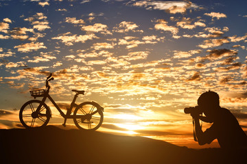 Silhouette of photographer taking pictures a bicycle at sunset background.