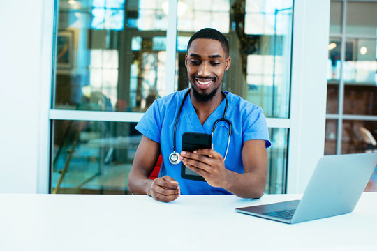 Portrait of a friendly male doctor or nurse wearing blue scrubs uniform and stethoscope sitting at desk with laptop in hospital checking mobile phone